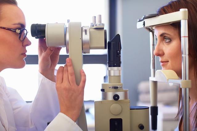 منظر جانبي لأخصائي عيون وسيدة شابة تنظر من خلال جهاز فحص العين