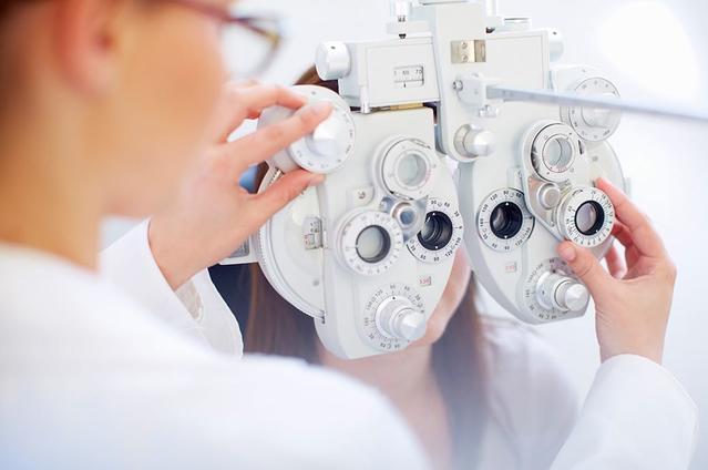 سيدة شابة خلف جهاز فحص العين بينما يفحص طبيب العيون عينيها خلال إجراء فحص العين.