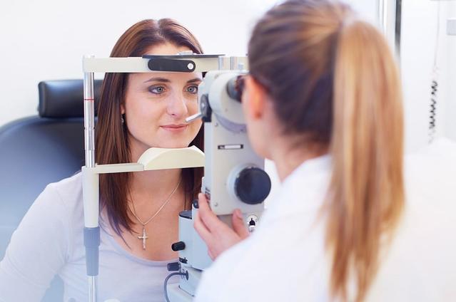 تركز الكاميرا على سيدة شابة تنظر من خلال كاميرا شبكية بينما ينظر أخصائي العيون عبر الجانب الآخر.